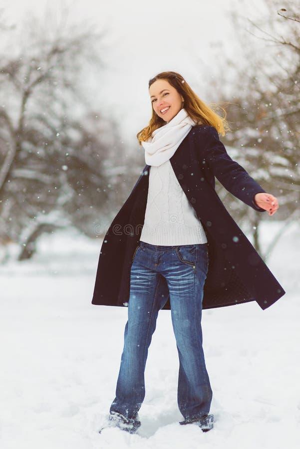 Estación, la Navidad, días de fiesta y concepto de la gente - la mujer joven sonriente en invierno viste al aire libre imagen de archivo