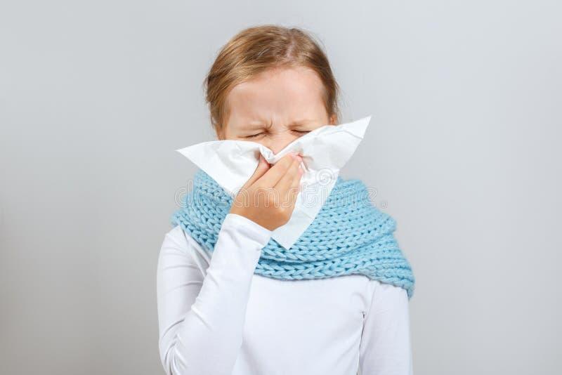 Estaci?n fr?a. Niña en una bufanda caliente se golpea la nariz. Un ni?o en un fondo gris imagenes de archivo