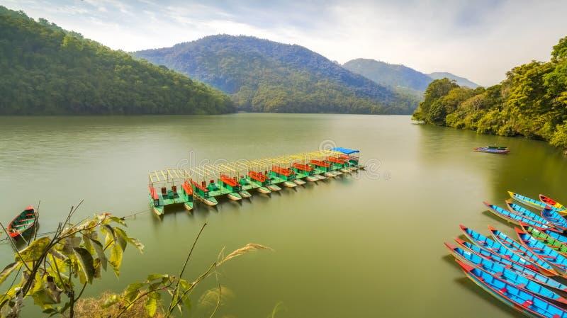 Estacionamento do barco do pedal no meio do lago e para cercar o monte verde foto de stock royalty free