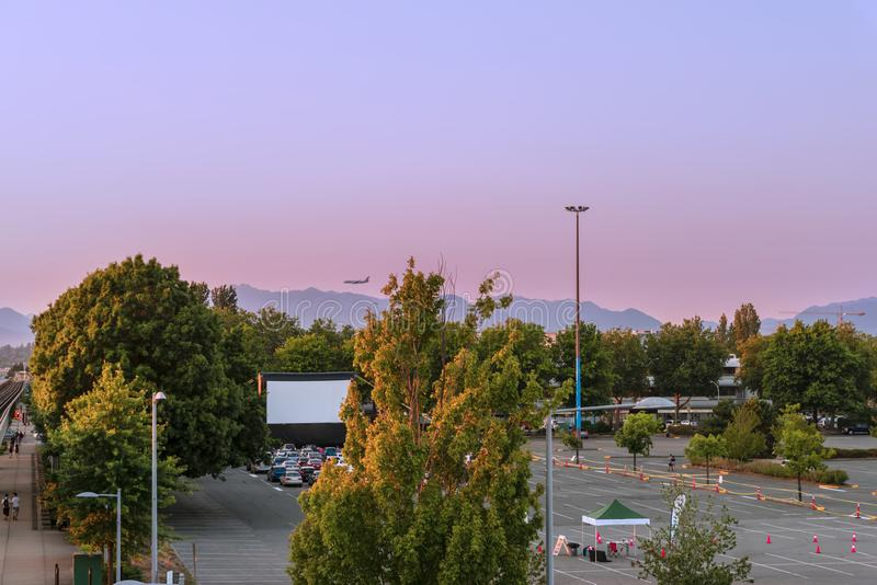 Estacionamento do carro com cinema do verão, árvores verdes, montanhas, voo p fotos de stock