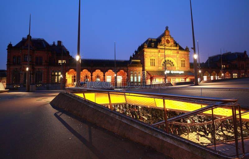 Estacionamiento de la bici por la estación de tren en la noche fotografía de archivo libre de regalías