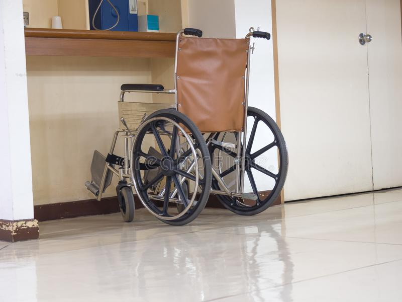 Estacionamiento de la silla de ruedas en el frente del teléfono público azul en hospital Silla de ruedas accesible para la gente  foto de archivo libre de regalías
