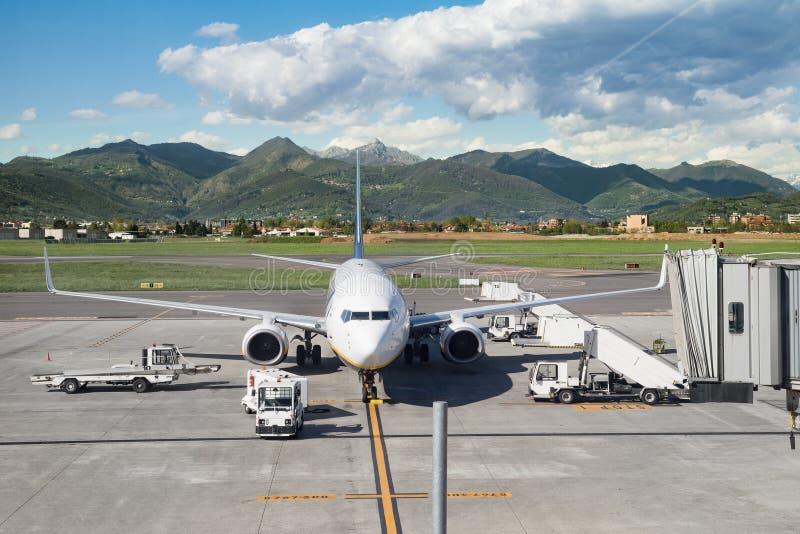 Estacionamiento del aeroplano de Airacraft en el aeropuerto cerca de las montañas verdes que son cargadas fotografía de archivo