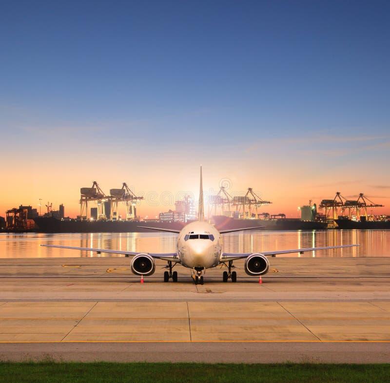 Estacionamiento del avión de carga en pistas del aeropuerto y puerto de envío detrás fotografía de archivo