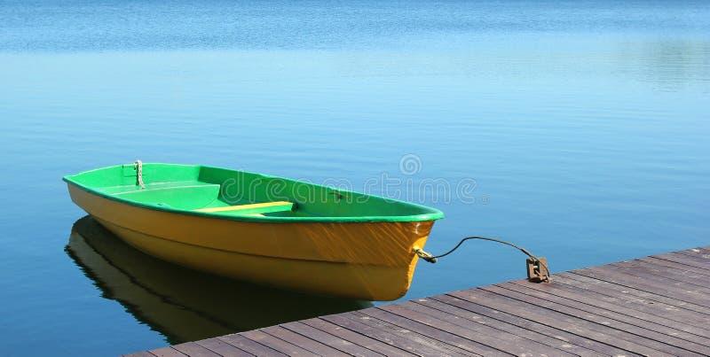 Estacionamiento del bote pequeño en un muelle de madera imágenes de archivo libres de regalías
