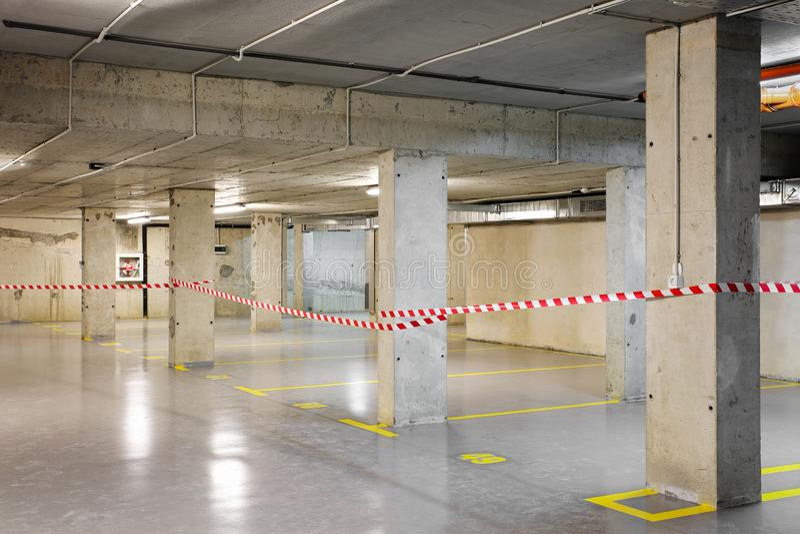 Estacionamiento subterráneo renovado del coche con la marca amarilla de la porción y la cinta amonestadora fotos de archivo