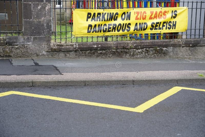 Estacionar em ziguezagues é sinal perigoso e egoísta fora da escola para a segurança rodoviária das crianças imagem de stock