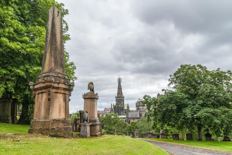 Estacione com túmulos e catedral dentro para trás em Glasgow Necropolis, Sco foto de stock royalty free