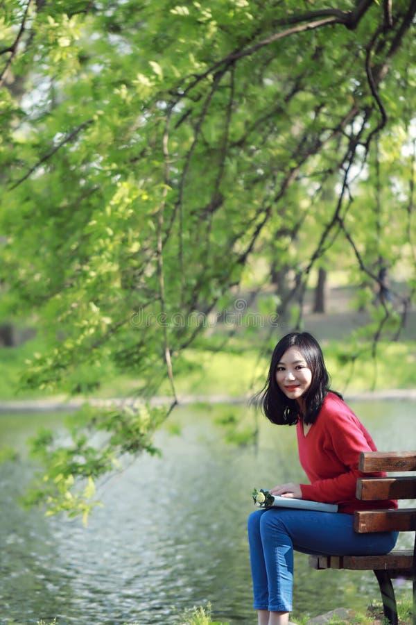 Estacione o livro de leitura da mulher no sorriso do banco feliz na câmera Mulher multicultural consideravelmente nova que apreci foto de stock royalty free