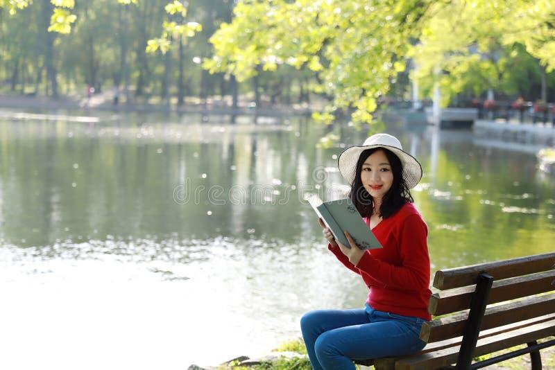 Estacione o livro de leitura da mulher no sorriso do banco feliz na câmera Mulher multicultural consideravelmente nova que apreci fotos de stock