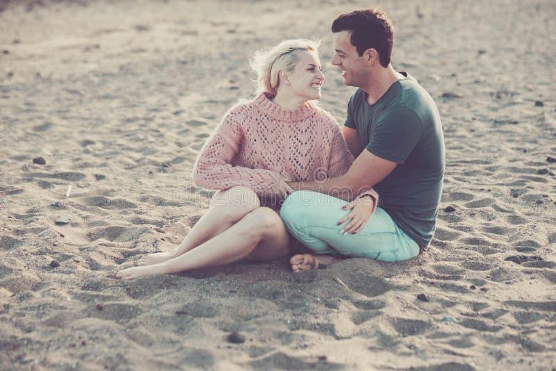 Estada caucasiano da jovem senhora e do homem dos pares modelo bonitos no amor que abra?a e que senta-se na praia louro e cabelo  imagem de stock royalty free