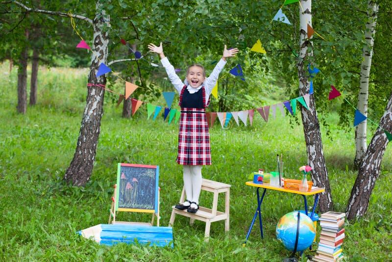Estada da menina da criança da criança da estudante na cadeira com suas mãos acima do hea foto de stock royalty free
