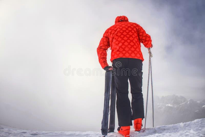Estada do esquiador com os esquis na borda da montanha acima do vale profundo da inclinação fotos de stock royalty free