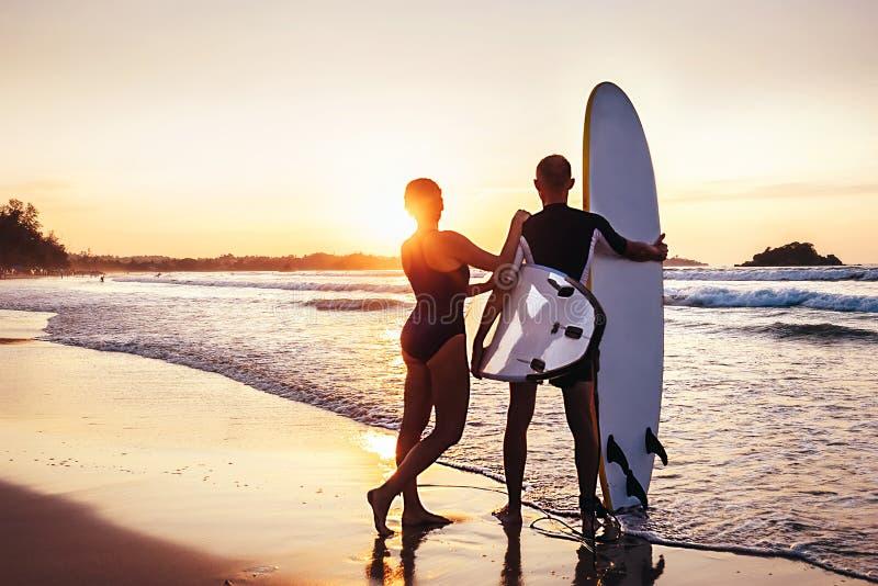 Estada dos surfistas dos pares na praia do oceano do por do sol imagens de stock royalty free
