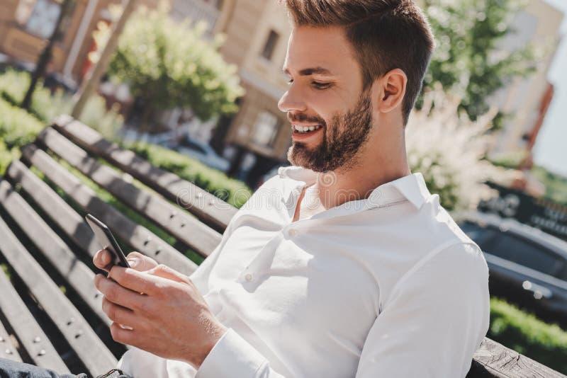 Estada no toque Homem novo que senta-se no parque e que olha seu telefone Conceito do sucesso fotografia de stock