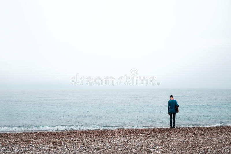 Estada sozinha do menino perto do mar imagem de stock