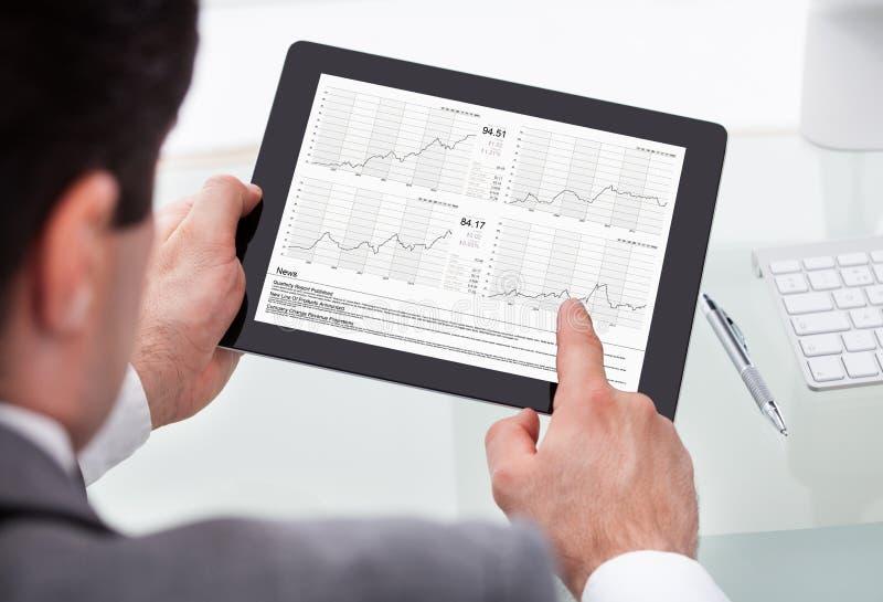 Estado de Analyzing Stock Market do homem de negócios na tabuleta de Digitas imagem de stock royalty free
