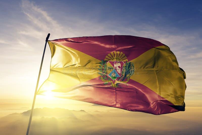 Estado de Aragua de tela de pano de matéria têxtil da bandeira da Venezuela que acena na névoa superior da névoa do nascer do sol ilustração do vetor