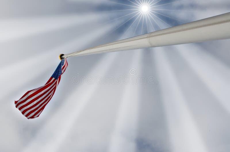 Estados Unidos señalan por medio de una bandera bajo rayos del sol foto de archivo libre de regalías