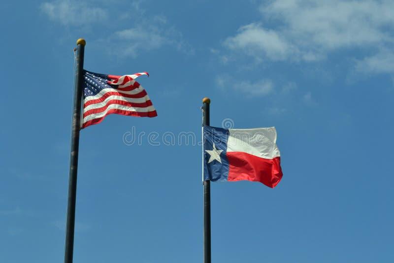 Estados Unidos y Texas Flags Against Blue Sky fotografía de archivo