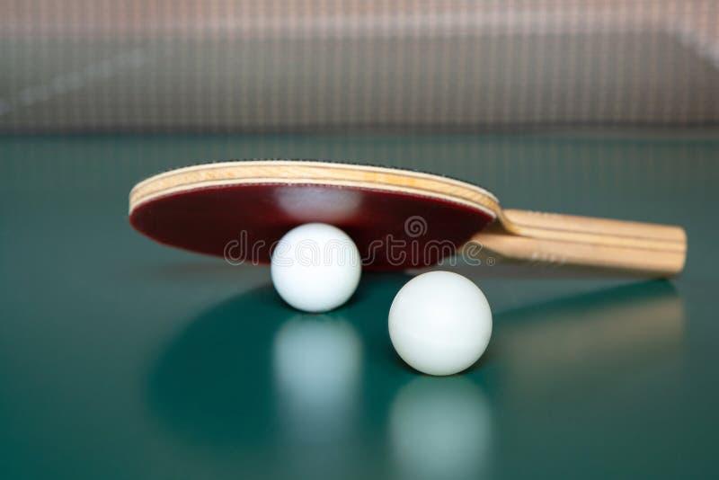 Estafa del ping-pong y dos bolas en una tabla verde Red del ping-pong imagen de archivo libre de regalías