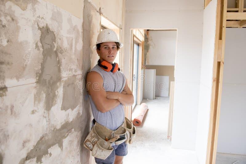 Estagiário atrativo e seguro novo do trabalho do construtor e do construtor que aprende e que trabalha no colarinho azul industri imagem de stock royalty free