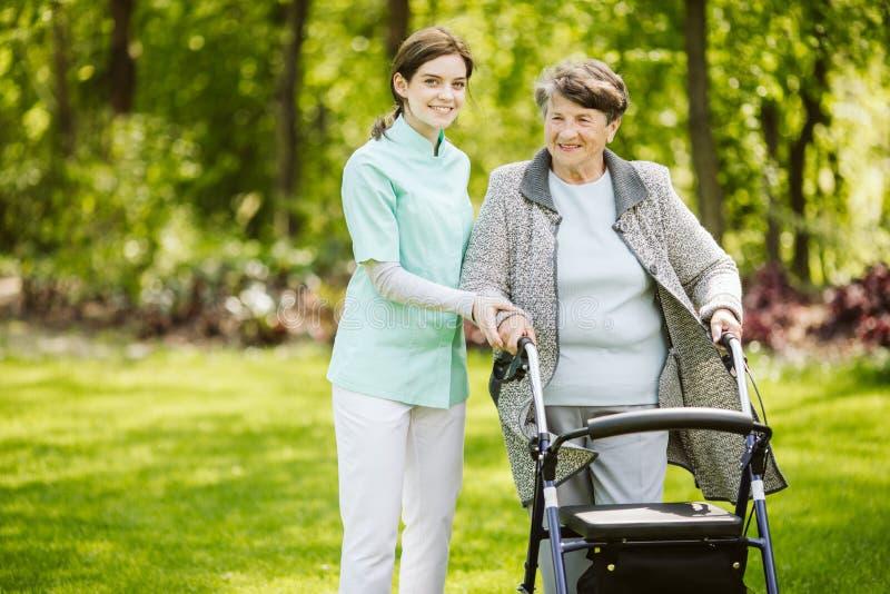 Estagiário fêmea novo com o paciente no lar de idosos fotos de stock