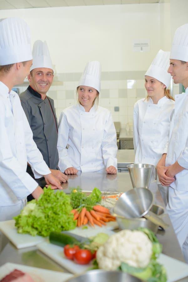 Estagiários na cozinha com cozinheiro chefe foto de stock