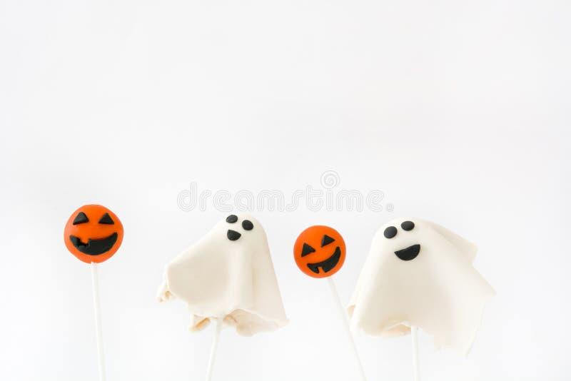 Estallidos de la torta de Halloween con la forma del fantasma y de la calabaza aislada en el fondo blanco foto de archivo libre de regalías