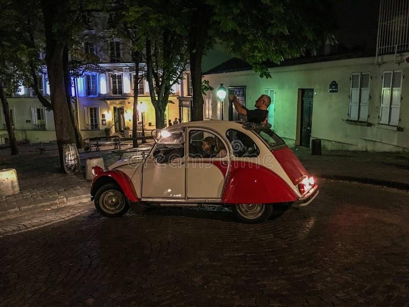 Estallidos del hombre fuera de una Citroen para tomar una foto de una calle de París en la noche fotografía de archivo libre de regalías