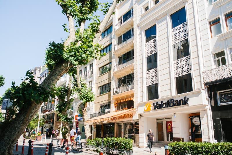 Estambul, el 17 de junio de 2017: Calle de la ciudad con un edificio y tiendas de banco La gente camina abajo de la calle Vida de imágenes de archivo libres de regalías
