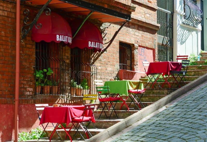 Estambul, Turquía - 20 de septiembre de 2018 Las tablas multicoloras del café del verano en las escaleras se inclinan en Balat fotos de archivo