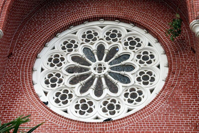 Estampado de plores blanco del mortero del círculo con el vitral y el ladrillo rojo del exterior del aguilón de la iglesia en la  imágenes de archivo libres de regalías