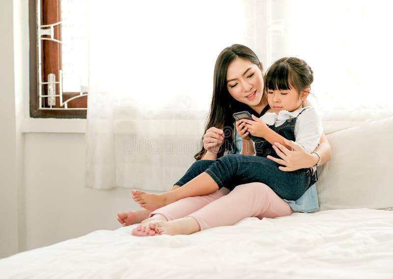 Estancia asiática de la madre y de la hija en la cama blanca y mirada al teléfono móvil y gozar junto fotos de archivo libres de regalías
