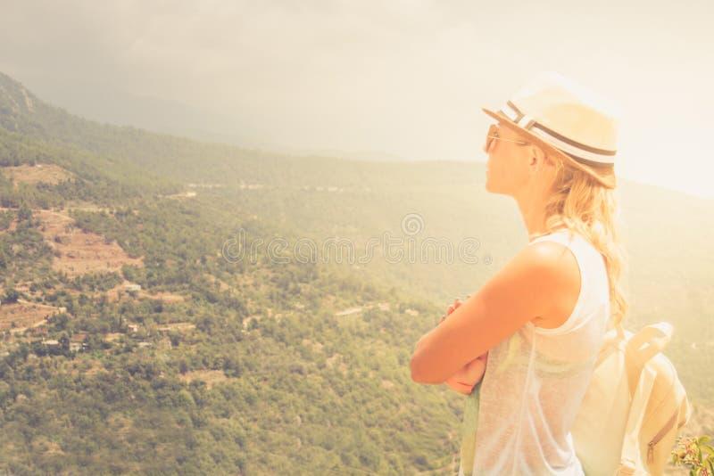 Estancia de la mujer joven en el borde del acantilado que mira sobre la vista expansiva de llanos y de montañas foto de archivo