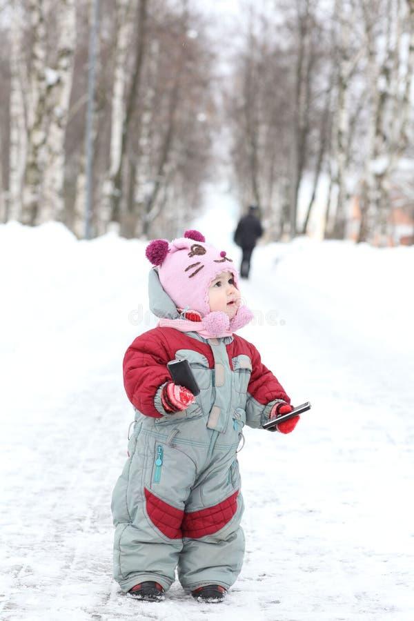 Estancia del bebé en el camino en parque del invierno imagenes de archivo