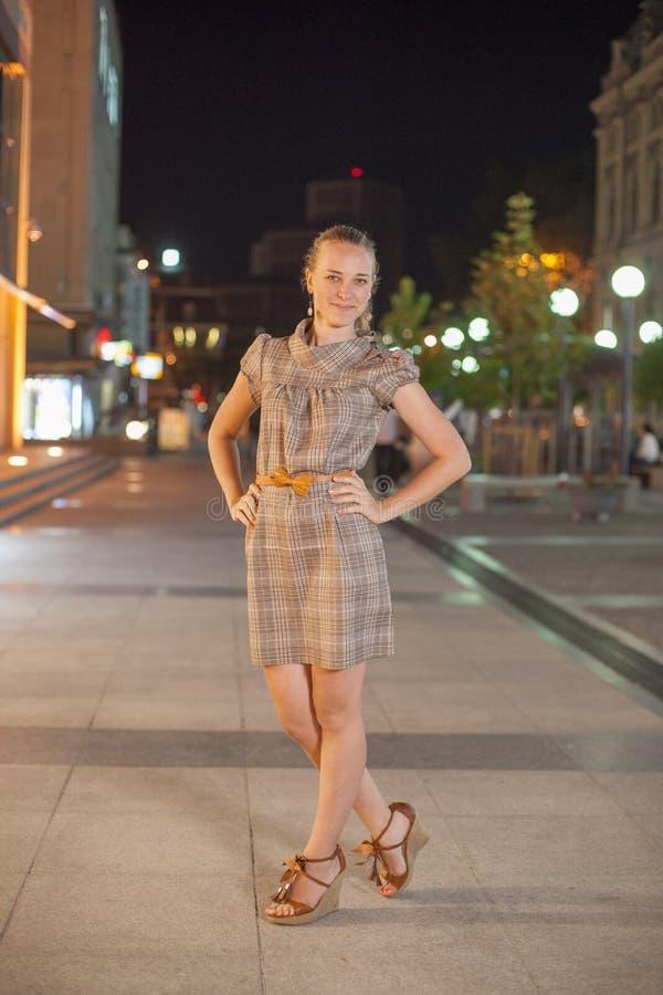Estancia hermosa de la muchacha en el cuadrado en la noche fotografía de archivo