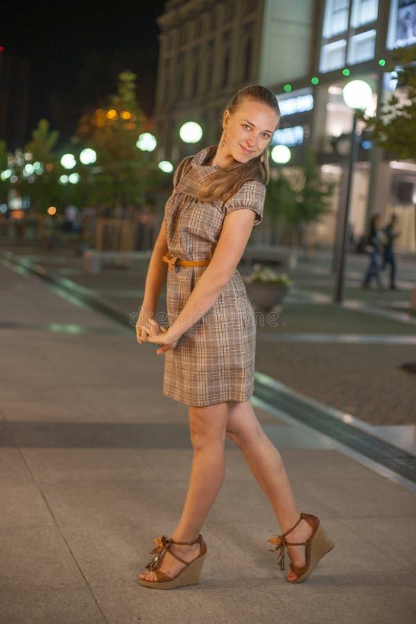 Estancia hermosa de la muchacha en el cuadrado en la noche fotografía de archivo libre de regalías