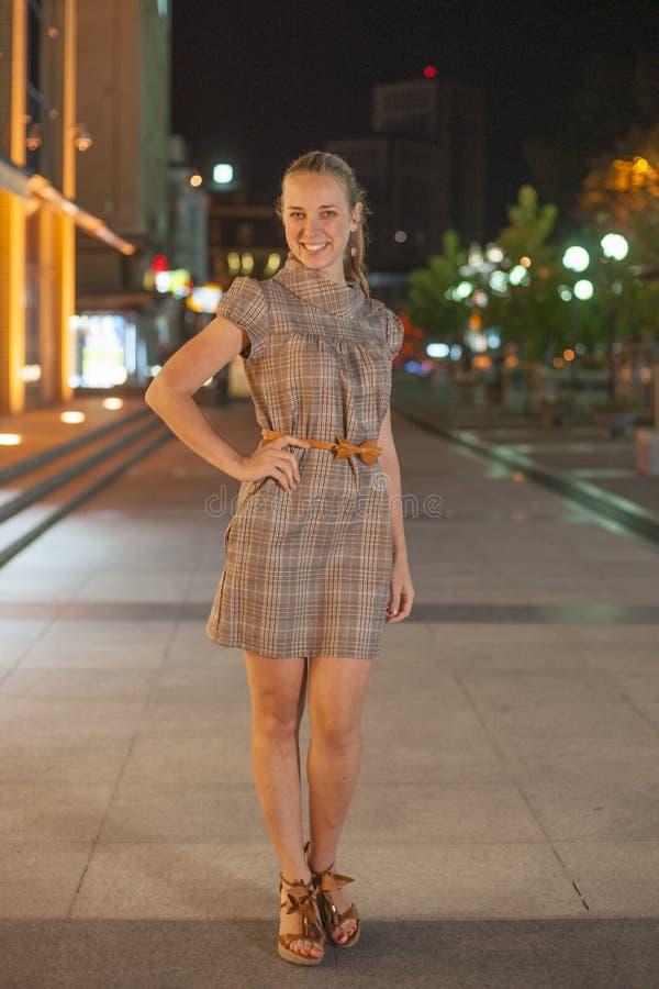 Estancia hermosa de la muchacha en el cuadrado en la noche imagen de archivo