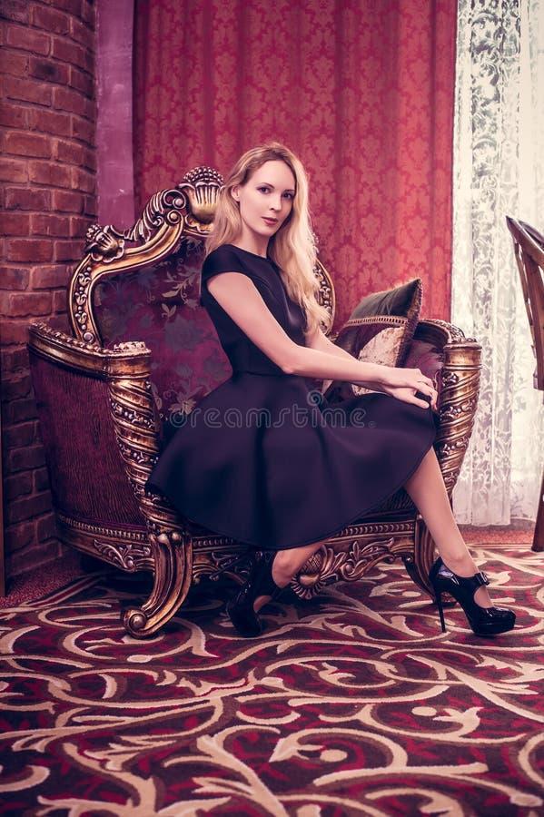 Estancia hermosa joven de la muchacha en una sala de estar de lujo imagen de archivo