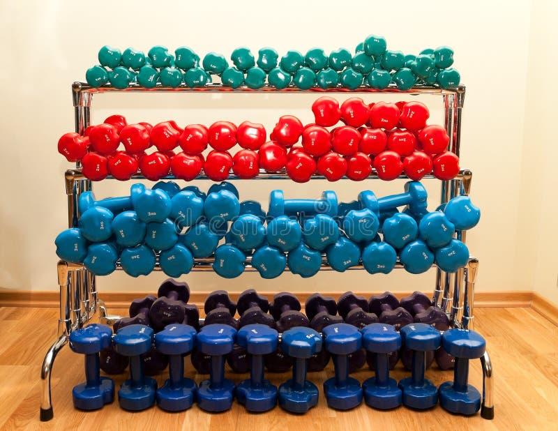 Estante con pesas de gimnasia coloreadas foto de archivo libre de regalías