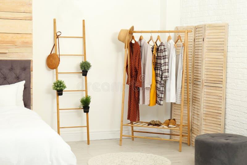 Estante de madera con ropa en interior del dormitorio imágenes de archivo libres de regalías