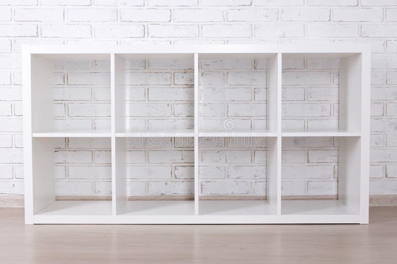 Estante de madera moderno sobre la pared de ladrillo blanca fotos de archivo