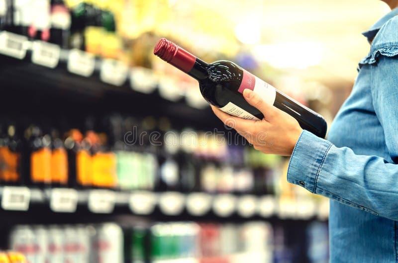 Estante del alcohol en licorería o supermercado Mujer que compra una botella de vino tinto y que mira bebidas alcohólicas en tien imagen de archivo libre de regalías