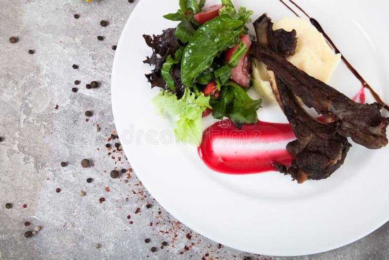 Estante del cordero con los purés de patata y las verduras, salsa roja en una placa blanca imágenes de archivo libres de regalías