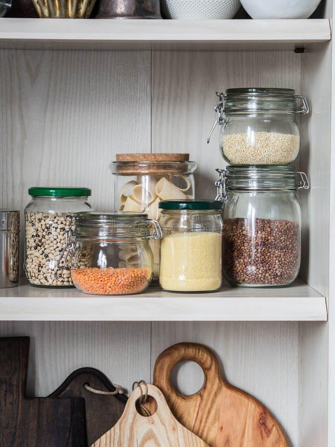 Estante en la cocina con los diversos tarros de cereales y de tajaderas de la cocina Tarros de cristal con las pastas, lentejas,  fotos de archivo