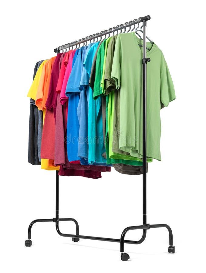Estante móvil con la ropa del color aislada en el fondo blanco El fichero contiene un camino al aislamiento imagen de archivo libre de regalías