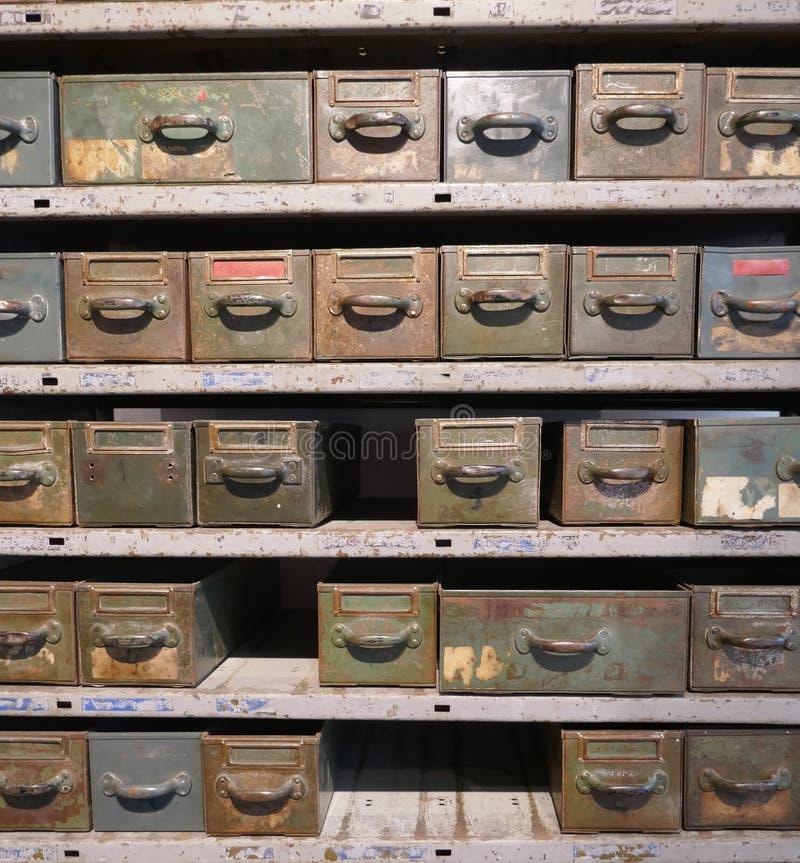 Estante oxidado viejo con muchos cajones y cajas para en un taller averiado imagenes de archivo