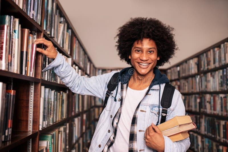 Estante que hace una pausa del estudiante universitario en la biblioteca fotos de archivo