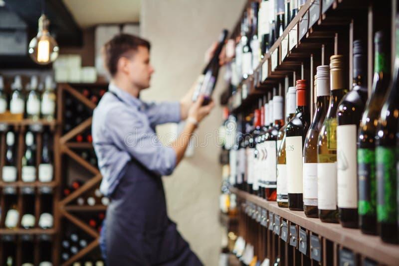 Estantes con el vino de la élite y el sommelier joven pensativo defocused imagen de archivo libre de regalías